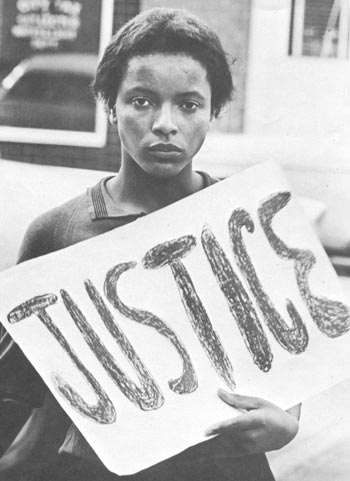 A picture of a young Afro-American woman holding a poster reading justice.
